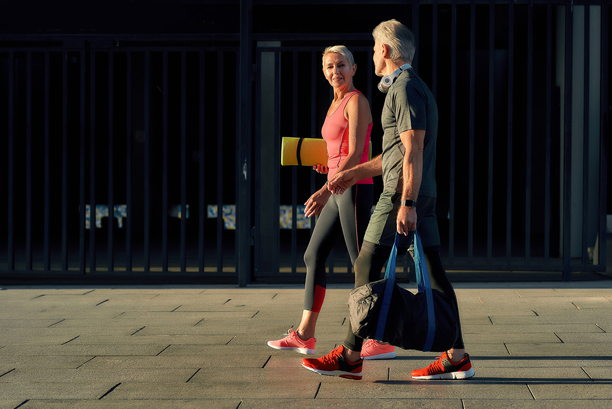 We always motivate each other. Full length of active middle-aged couple in sports clothing going home after active training together