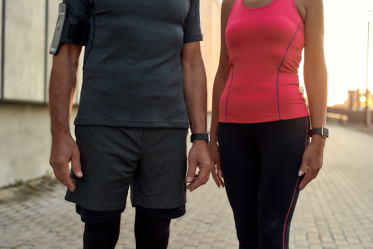 Cropped photo of a couple in sports clothing standing together outdoors
